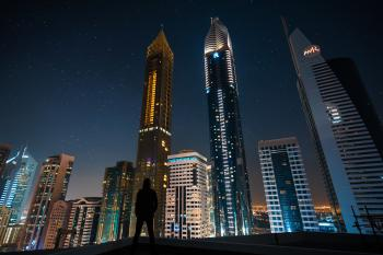 Man Standing in Assorted Building String Light during Night Time