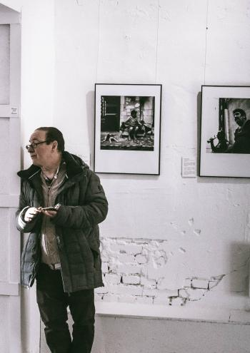 Man Standing in Front of Grayscale Gallery Photo
