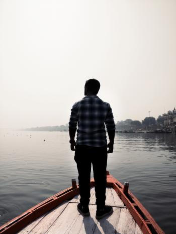 Man Standing On Wooden Boat