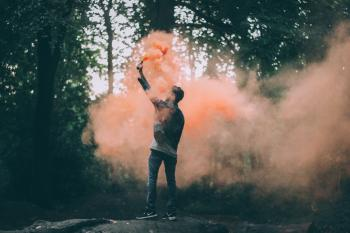 Man Throwing Peach-colored Powder