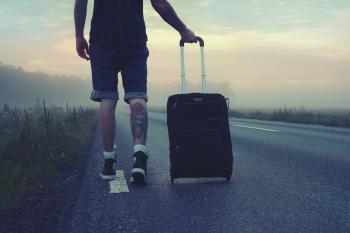 Man Walking on the Road Holding Black Luggage during Sunset