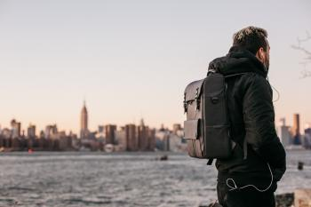 Man Wearing Black Bubble Jacket and Black Leather Backpack Near Bay