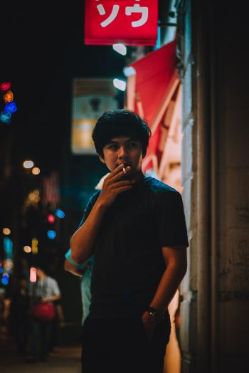Man Wearing Black Crew-neck Shirt Holding White Cigarette during Night Time