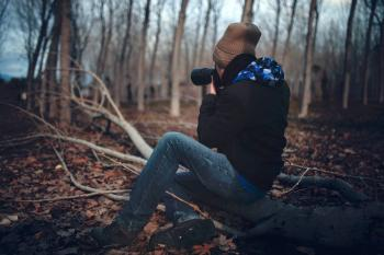 Man Wearing Black Jacket and Blue Jeans Sitting on Tree Branch