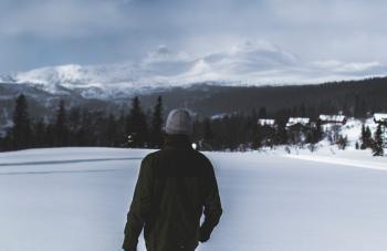 Man Wearing Black Jacket Walking in the Snow
