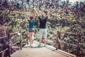Man Wearing Black Shirt Beside a Woman in Green Shirt Raising Their Hands in the Air