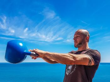Man Wearing Black Shirt Holding Kettle Bell Near Body of Water