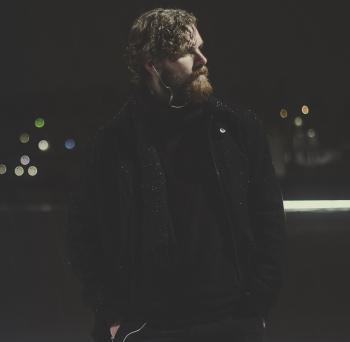 Man Wearing Black Zip-up Jacket Taking Picture during Nighttime