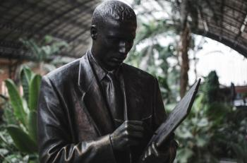 Man Wearing Blazer Holding Book and Pen Statue