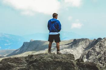 Man Wearing Blue Hoodie Standing on Top of Mountain