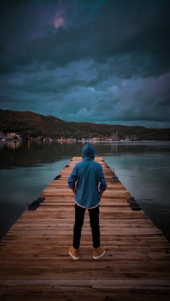 Man Wearing Blue Hoodie Standing On Wooden Dock