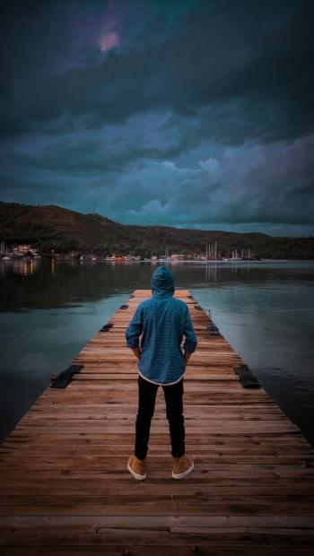 Man Wearing Blue Hoodie Standing On Wooden Dock