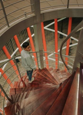 Man Wearing Gray Long-sleeved Top Walking Downstairs