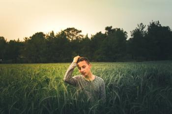 Man Wearing Gray Sweatshirt Standing On Grass Field