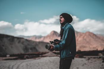 Man Wearing Jacket Holding Dslr Camera on Desert