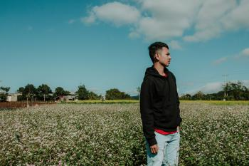 Man Wearing Pullover Hoodie Standing on Flower Field