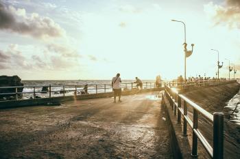 Man Wearing White Shirt Walking on Concrete Pavement Near Sea