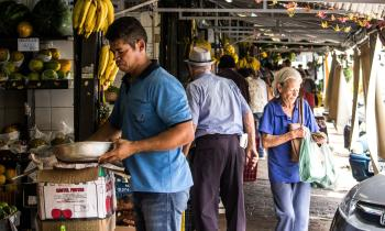 Man Wears Blue Polo Shirt Holding Gray Metal Bowl Near Assorted Fruits