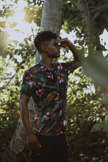 Man Wears Multicolored Floral Button-up Short-sleeved Shirt Beside Tree