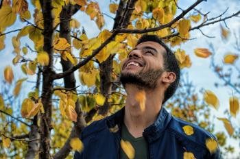 Man With Blue Denim Zip-up Jacket Near Yellow Leaf Tree
