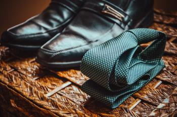 Man's Black Leather Shoes Near to Green and White Spotted Tie