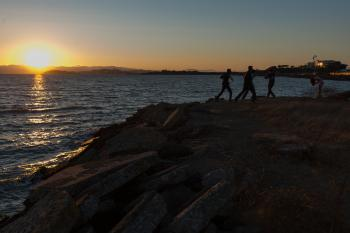 Men dancing on rocky outcrop in front of setting sun