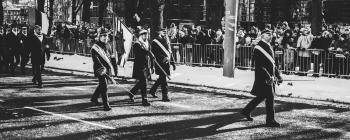 Men Walking on Streets Carrying Flag during Parade In Grayscale Photo