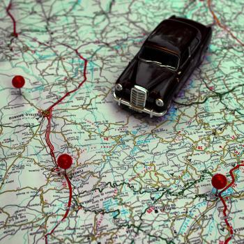 Miniature car and pushpins on a map - Travel concept