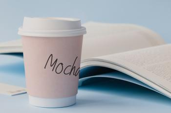Mocha Labeled White Disposable Coffee Cup Beside Book