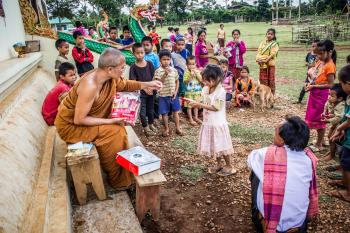 Monk in Front of Children Near Brown Concrete Building