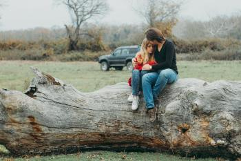 Mother and Daughter Sitting on Tree Log