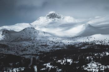 Mountain Coated With Snow Under Gray Sky