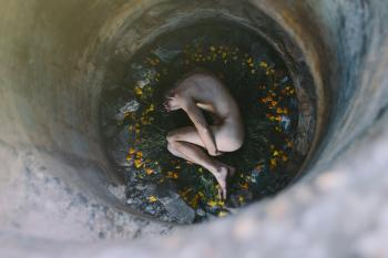 Nude Person Inside Well Laying on Flowers
