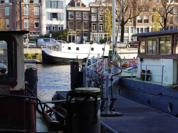 Old houseboats in the canal water of Amsterdam city