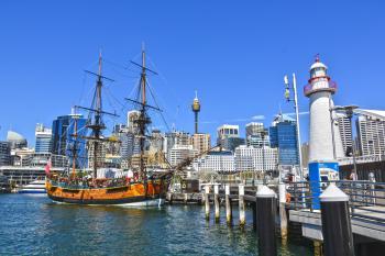 Orange Galleon Ship on Body of Water Beside City Buildings