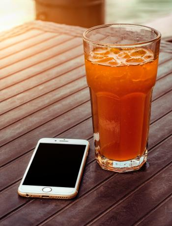 Orange Juice in Clear Drinking Glass Besides Gold Iphone 6 on Brown Wooden Table