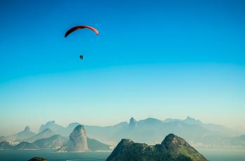 Panorama Photo of a Person Parachuting Above Volcano Lake during Daytime