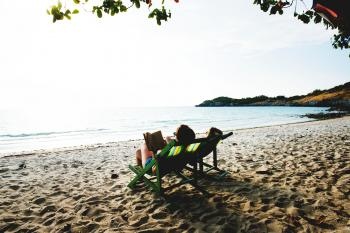 People Lying On Green Wooden Lounger Chairs On Beach