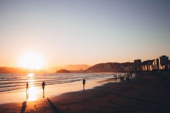 People Walking on Seashore during Golden Hour