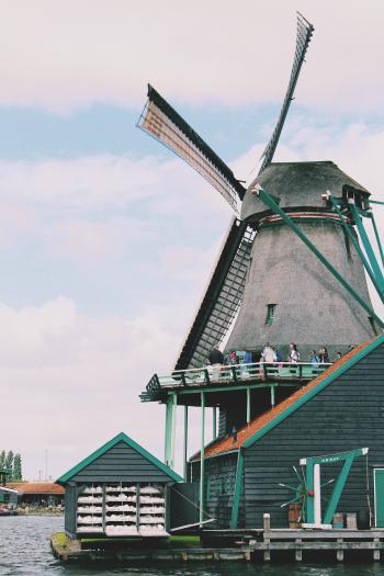 People Walking on Windmill Near Body of Water