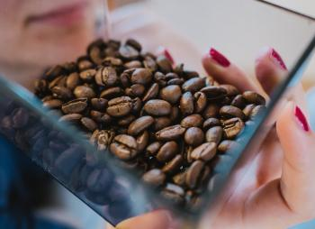 Person Holding Coffee Beans on Glass Bowl
