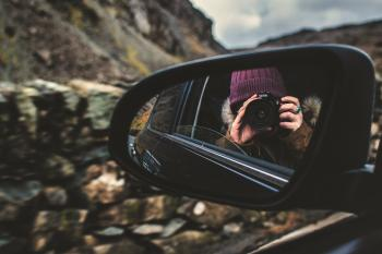 Person Holding Dslr Camera Reflected on Black Framed Wing Mirror