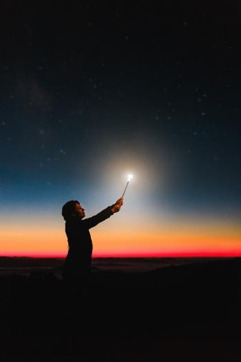 Person Holding Roman Candle at Night