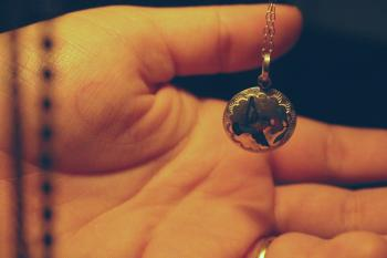 Person Holding Round Silver-colored Necklace Pendant
