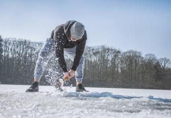 Person Holding Shovel on Snow Field