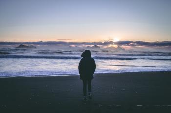 Person in Black Hoodie Near Seashore during Sunset