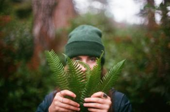Person in Green Cap Holding Fern Leaves