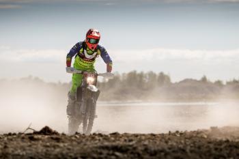 Person In Green Motocross Gear Riding A Dirt Bike