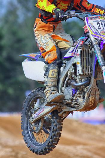 Person in Orange and Yellow Fox Motorcycle Suit Riding a Purple White Gray and Black Dirt Motorcycle Outdoors during Daytime