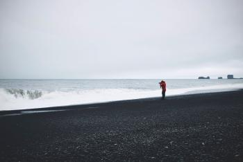 Person in Red Top Standing Near Body of Water